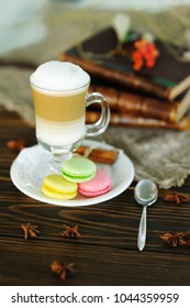 latte and macaroons close-up on a wooden background on a background of old books and burlap