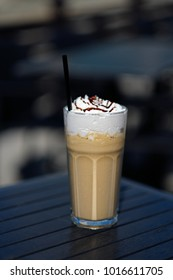 latte macchiato coffee with cream in tall glass with straws on table