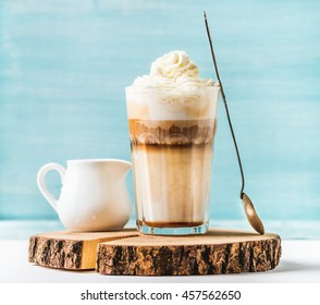 Latte macchiato with whipped cream, serving silver spoon and pitcher on wooden round board over blue painted wall background, selective focus, horizontal composition