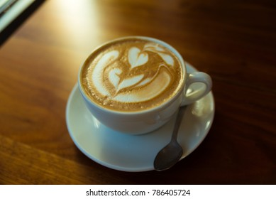 Latte in a white cup on the wooden table