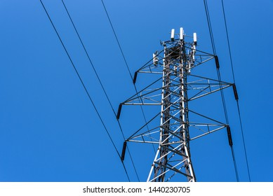 Lattice self-supporting steel utility tower with power lines and panel antennas for a wireless communications network, bird nest on top, bright blue clear sky background