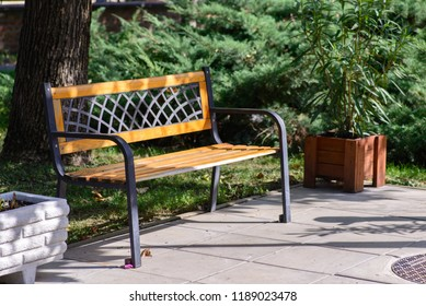 A lattice-patterned bench in a park.