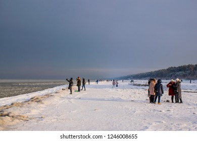 Jūrmala / Latvia - Dec 2015: Tourists ad locals on the beach of Baltic sea in famous Baltic resort at Christmas time. Winter in Baltic States.