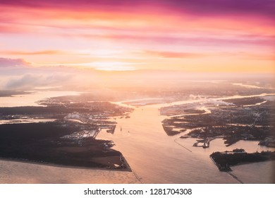 Latvia, Europe. Aerial View Of Western Dvina Flows Into Baltic Sea Near Riga During Winter Sunrise. Aerial View From Airplane Flight. Sunset Sunrise Over Gulf Of Riga, Bay Of Riga. Beautiful Landscape