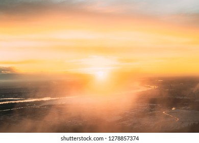 Latvia, Europe. Top Aerial  View Of Sunset Sunrise Above Winter Earth. Aerial View From High Altitude Flight Of Aircraft On Sunny Sunset Sunrise In Winter. Sunny Dawn Sky.