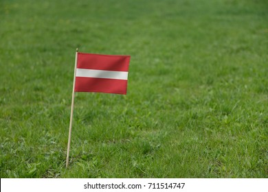 Latvia flag, Latvian flag on a green grass lawn field background. National flag of Latvia waving outdoor
