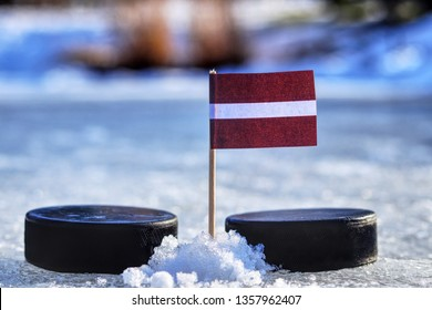 Latvia flag on toothpick between two hockey pucks. Winter classic. Flag on frozen pond on unkempt ice. Traditional pucks for international matches.