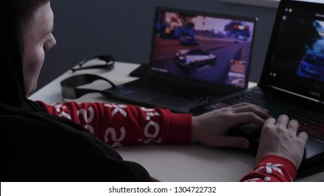 Latvia, Jurmala - 11 January 2019:A young guy (male) player plays a professional player on the GTA tournament on two laptops. Concept of: New games, Gambling addiction, Dependence, GTA, Racing.