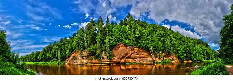 Latvia, Sigulda, Velna cliff, Gauja river. Panorama view of the forest, trees on the edge of the Velna sandstone cliff along the Gauja river in the summer time.