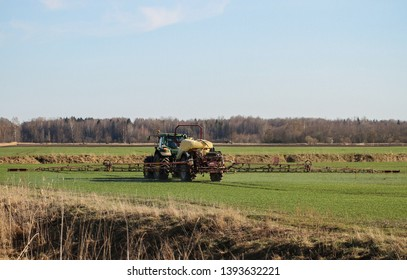 LATVIA, TUKUMS - 19 APRIL: Tractor work on the field in a springtime, spraying a chemicals on 19 April 2019, Tukums district, Latvia.