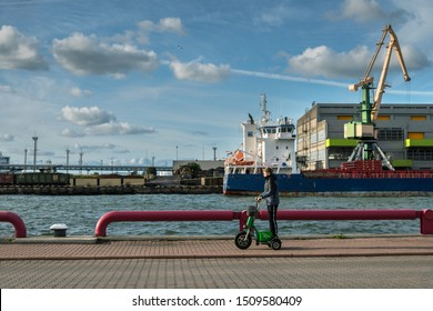 LATVIA, VENSPILS - 14 SEPTEMBER: Ventspils is a city in Latvia, situated on the Venta River and the Baltic Sea. View to coast of Venta with boy riding by scooter on 14 September 2019,Venspils, Latvia.