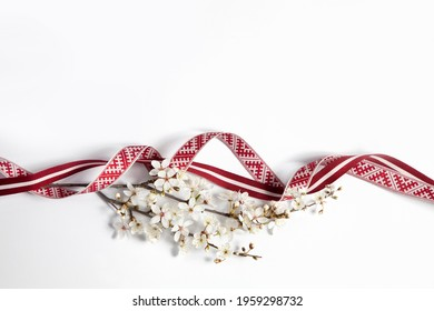 Latvian national celebration decoration with a flourishing branch made of Latvian flag ribbon and Lielvarde belt ribbon for independence day of Latvia