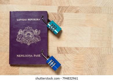 "Latvian non-citizen purple passport locked with combination locks, concept, The words ""LATVIJAS REPUBLIKA"", ""NEPILSONA PASE"" (Latvian) meaning Republic of Latvia, Alien's passport. - Shutterstock ID 794832961"