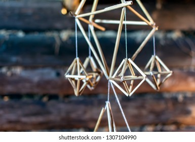 Latvian Puzurs hanging in the dark log hut. Puzurs is traditional Latvian room decoration made of reeds or straws. It is solstice symbol similar to Finnish Himmeli and Lithuanian Siaudinis Sodas.