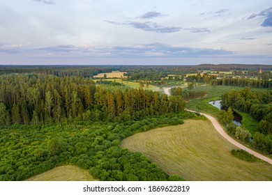Latvian rural landscape with agricultural fields, forests and roads at sunset, aerial top view, soft focus aerial photoshot