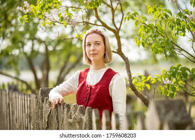 Latvian woman in traditional clothing posing on nature background in village. Ligo festival. Riga. Latvia