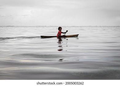 Lau Lagoon, Malaita Province, Solomon Islands - December 10, 2016: A young boy paddles his dugout canoe through Lau Lagoon, on the eastern coast of Malaita Province in the Solomon Islands.