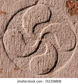 Lauburu, the ancient traditional basque cross symbol engraved in stone