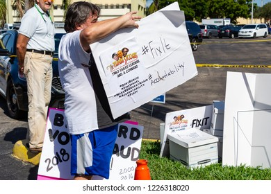 """LAUDERHILL, FLORIDA, USA - NOVEMBER 10, 2018: A man holds a """"Three Stooges"""" parody sign in a vote counting protest outside Broward County Supervisor of Elections Brenda Snipes' office"""