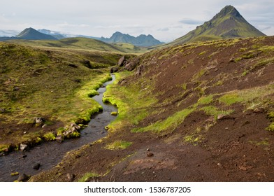Laugavegur hiking trail. A brook at the foot of Storasula. Volcanic landscape with green moss. Highlands of Iceland. Segment of the trail between Alftavatn and Hvanngil. Myrdalsjokull at the horizon