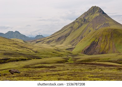 Laugavegur hiking trail. Foot of Storasula mountain. Volcanic landscape with green moss. Highlands of Iceland. Segment of the trail between Alftavatn and Hvanngil. Myrdalsjokull at the horizon