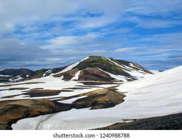 Laugavegur trail (Laugavegurinn) goes throw colorful rhyolite mountains and black lava field in active geothermal area Jokultungur, near Landmannalaugar, Fjallabak Nature Reserve, Highlands of Iceland