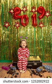 laugh little girl sit on retro suitcase christmas tinsel background