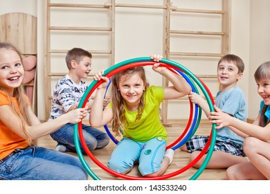 Laughing active children holding hula hoops