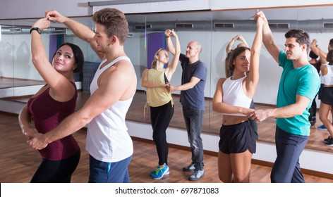 Laughing adults dancing bachata in dance studio