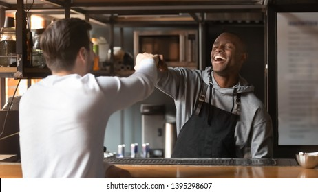 Laughing African American barista fists bumping with customer in cafe, excited bartender wearing apron standing behind bar counter, greeting friend or regular customer in coffeehouse