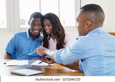 Laughing african american couple with contract of agent at new home