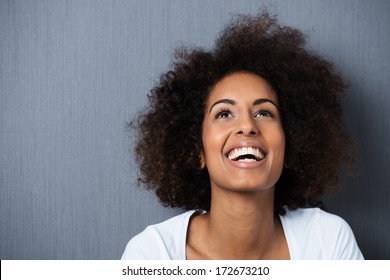 Laughing African American woman with an afro hairstyle and good sense of humor smiling as she tilts her head back to look into the air