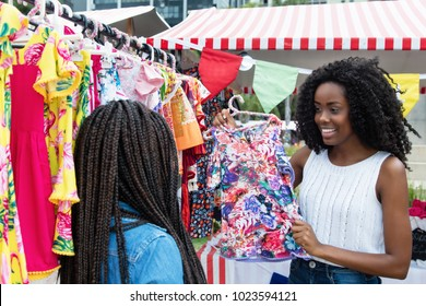 Laughing african american woman presenting colorful clothes to client outdoors at typical traditional market