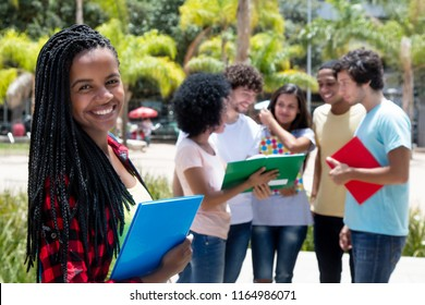 Laughing african female student with group of students outdoor on campus of university in summer