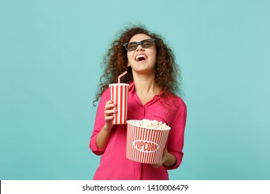 Laughing african girl in 3d imax glasses watching movie film hold popcorn cup of soda isolated on blue turquoise background in studio. People emotions in cinema, lifestyle concept. Mock up copy space