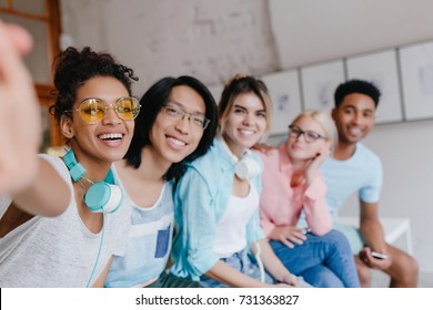 Laughing african girl in headphones and yellow glasses making selfie sitting on the bench with university mates. Excited female student taking picture of herself and her asian friend with long hair.