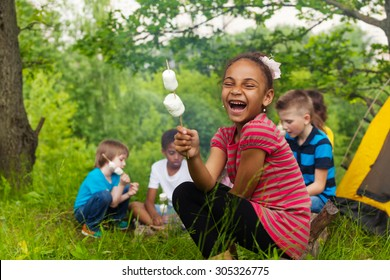 Laughing African girl holds stick with smores
