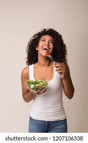 Laughing african-american woman eating healthy salad over light background