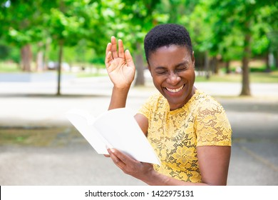 Laughing African-American woman reading joke in book. Happy beautiful woman spending time in park with book of funny stories. Literature concept