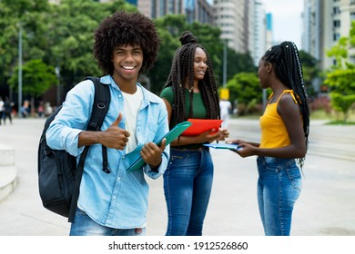 Laughing afro american male student with group of young adults outdoor in city in summer