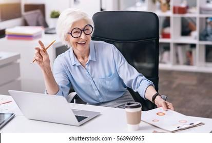Laughing aged woman enjoying her job