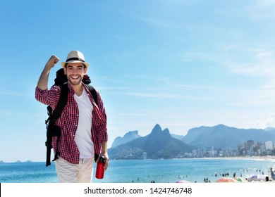 Laughing american hipster tourist at Ipanema beach at Rio de Janeiro with beach and mountain in summer