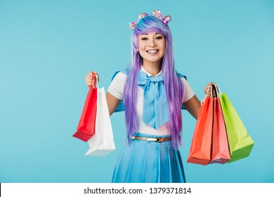 Laughing asian anime girl holding shopping bags isolated on blue