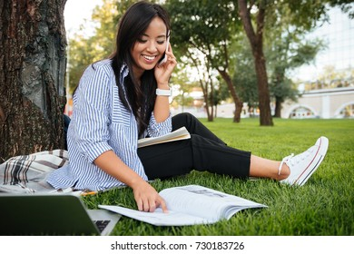 Laughing asian student in striped shirt talking on mobile phone, while sitting under the tree, outdoor