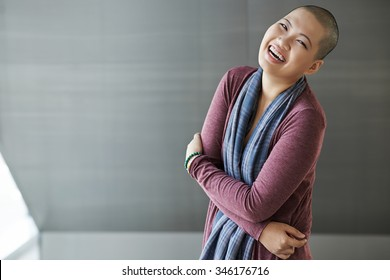 Laughing Asian woman with shaved head looking at camera
