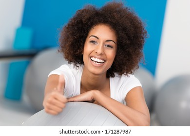 Laughing attractive African American woman with a wild afro hairstyle working out in a gym giving a thumbs up gesture of approval