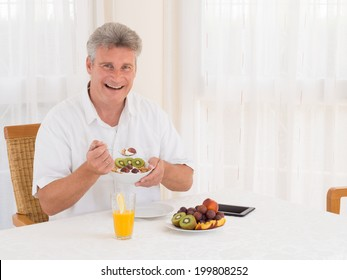 Laughing attractive mature senior man full of vitality sitting at the table eating a healthy breakfast of fresh fruit and cereal