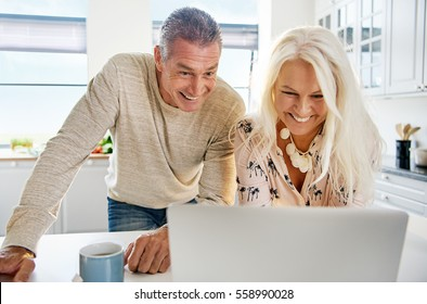 Laughing attractive middle aged couple looking at computer on counter top in kitchen with bright cabinets and windows