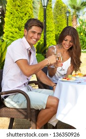 Laughing attractive young couple celebrating sitting at a table in the garden eating a healthy tropical fruit meal and drinking champagne