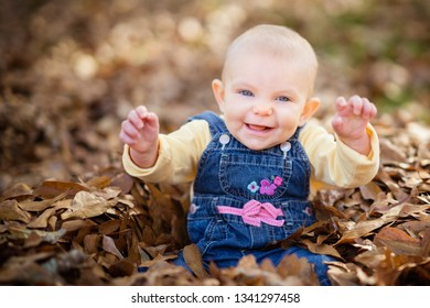 Laughing baby in fall leaves